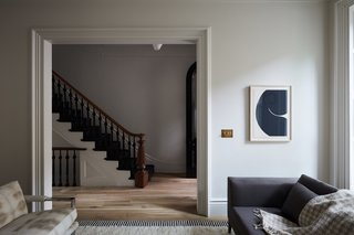 The large living room doorway was preserved and frames views of the original staircase that was restored with the treads, risers, and balustrades painted Benjamin Moore Black. The mahogany handrail was sanded down to its raw color and finished in a water-based clear coat.