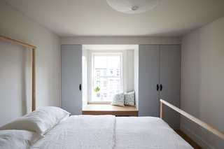 Custom closets painted Benjamin Moore Sterling were added to both kids' bedrooms. One room has a built-in window seat (pictured) and the other has a built-in desk.