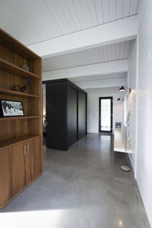 A compact bedroom is enclosed in the black volume just off of the entrance. A small bathroom lies adjacent.