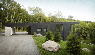 The home is clad in black-stained rough sawn cedar that has been sourced from Éco-Cèdre.