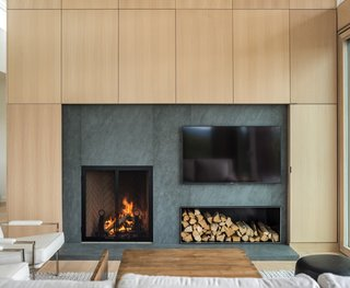 A custom wood-veneer paneled wall surrounds the wood-burning fireplace.