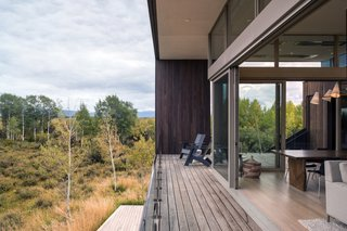 The covered porch wraps around the east and south sides of the home to overlook Teton views, as well as the pond and creek.