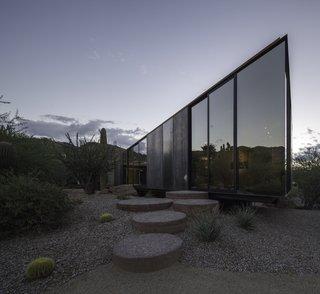 Round concrete blocks leading to a sliding door entrance contrast against the volume's unique angular shape.
