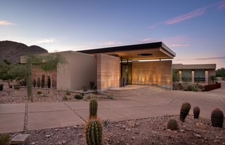 A dramatic roof overhang with Douglas Fir soffits and rammed earth walls frame the entrance.