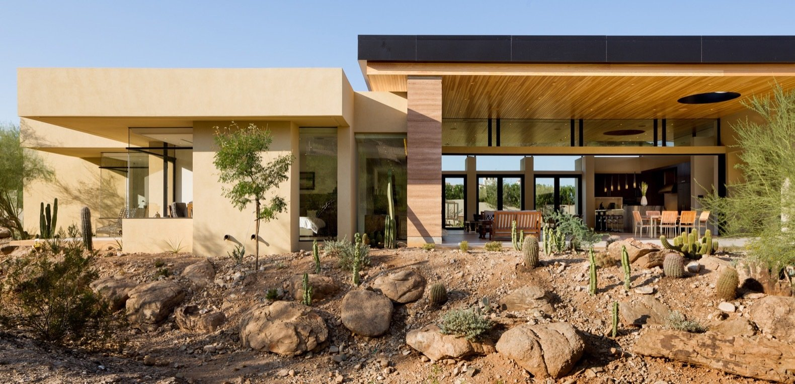 A north-facing view of the open great room and master suite to the left from the desert wash.