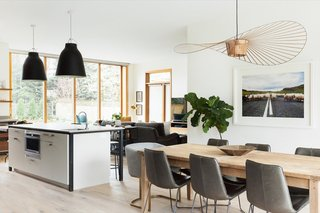 The Costance Guisset pendant adds a whimsical touch to the dining area, which has been furnished with a farmhouse-style table and West Elm dining chairs.