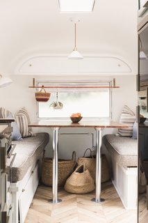 The dining space is located at the front of the trailer. The chevron flooring is Oak Fortress Rochesta by Kaindl and the upholstery is by Joybird.