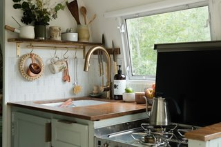 The Dometic Range oven has three burners and a glass lid for extra counter space. The walnut countertops were locally made by Adam Garret Designs.