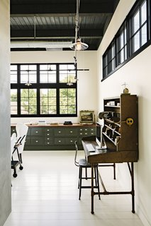 A vintage postoffice desk anchors one end of the office that's fitted with built-in cabinetry with a 16-foot-long walnut top on the far wall.