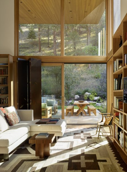 """""""The library space is positioned on the intimate courtyard nestled into the base of the butte,"""" note the architects. """"Here, an expressive, sheltering roof tilts up to capture natural light and rising views of the old-growth pine forest."""""""