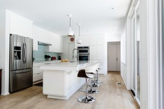 The modern kitchen feels much more bright and airy with greater access to natural light and all-white cabinetry.
