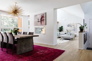 Walls were knocked down to connect the living room and dining area, while a see-through fireplace partitions the rooms. The bright fuchsia rug was a vintage find.