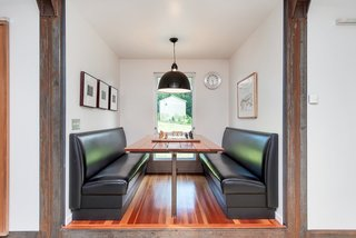 The banquette-style dining area features a built-in table and plush, leather seating.