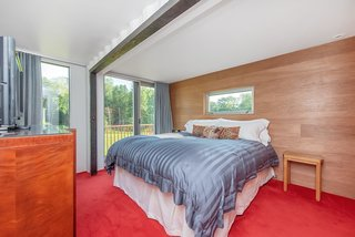 The master suite is wrapped in wood paneling and has a full-height wall of custom closet space.