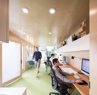The office interior features Flor carpet tiles and walls of pre-finished birch plywood.