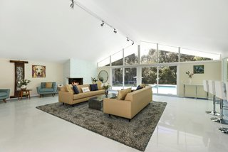 Lined with new terrazzo flooring edged with blue tile, the open-plan living room is anchored by a corner gas fireplace.
