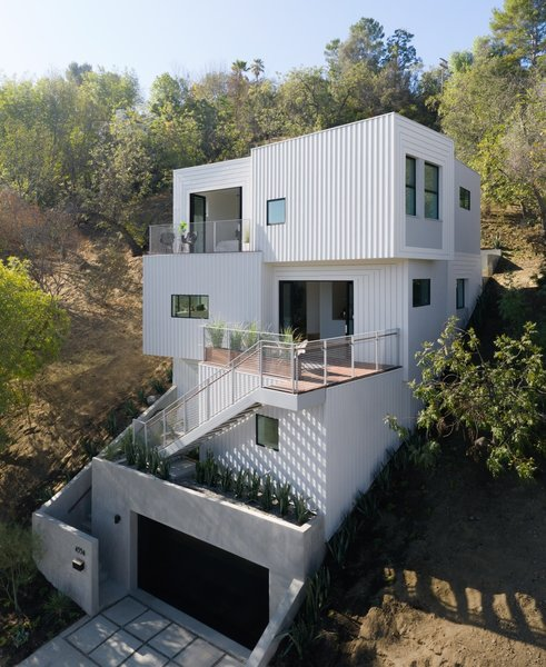 """The exterior cladding of the house is custom-made, a play on board-and-batten siding organized into patterns that suggest varied depth and texture,"" notes the firm. ""Painted in subtle gradations from white to gray, the striped shadows of the board-and-battens shift throughout the day. """