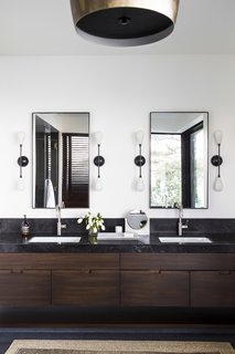 The master bath is fitted with custom teak cabinetry and Aged Petit Granit counters.