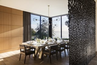 A custom bronze divider by artist Michele Oka Doner screens the formal dining room from the entry. The chandelier is by Lindsey Adelman Studio.