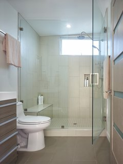 Porcelain tiles line the bathroom. The countertops and cabinetry are ceramic and wood veneer over fiberboard, respectively.