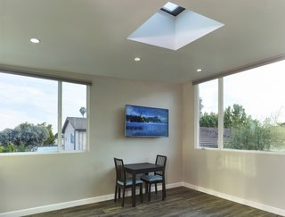 """To create a spacious feel, Martin installed large, double-glazed windows and a Velux skylight. """"The windows, together with the operable skylight, act as a solar chimney to passively cool the space,"""" he notes."""