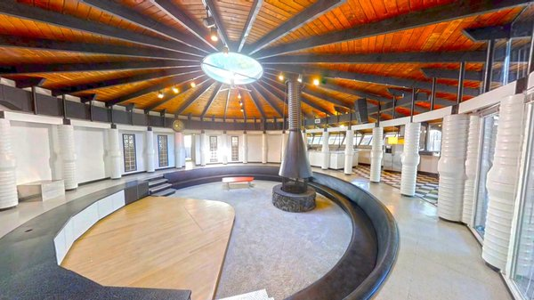 The timber ceiling slopes upwards to the round skylight. The built-in bench seating have been reupholstered and the steps were rebuilt with polished aluminum treads.