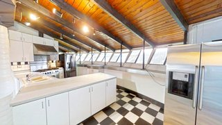 The kitchen features updated appliances and checkered ceramic tile flooring.