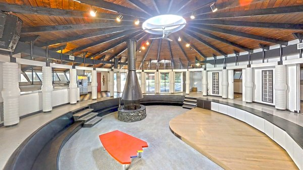 The music room, which now serves as the living room, is set beneath a central skylight and anchored by a free-standing hearth.