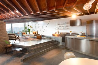 The raised living room steps down to the eat-in kitchen. Polished concrete floors are used throughout.