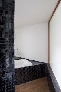 A peek inside a mosaic-tiled bathroom with a soaking tub.