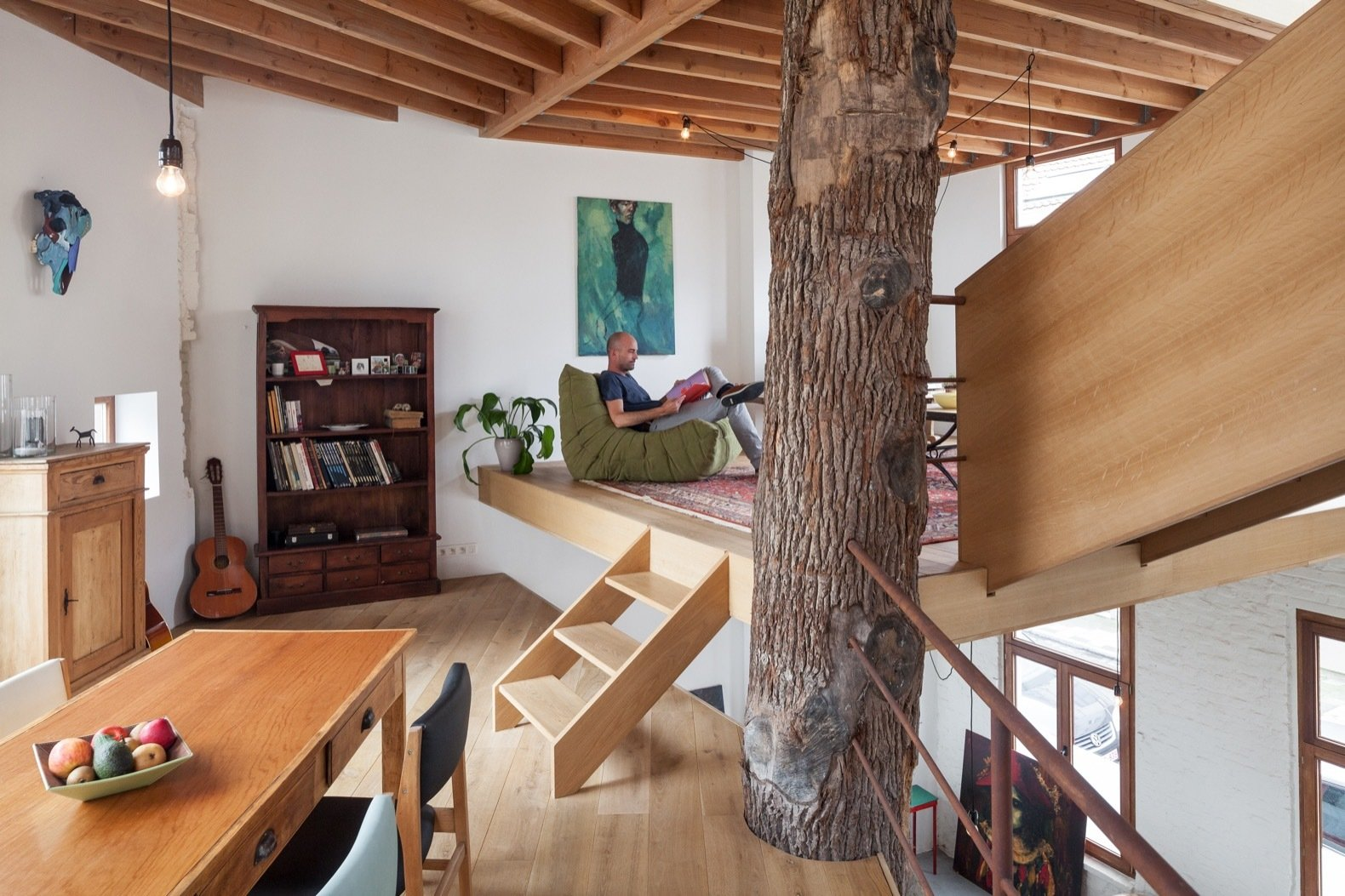 """The column had to be affordable and nice to look at,"" note the architects. ""So we bought a tree and put it right in the middle of the building. Between the tree and the facade, we have created new floors which are built in a spiral around the tree. This results in a very dynamic and open space."""