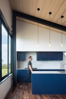 The kitchen is outfitted with Caesarstone counters and is completed with blue-painted walnut plywood cabinets.