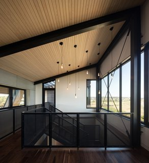 Walnut flooring has been used throughout the light-filled home. Here, a bridge connects the living spaces to the exterior deck and staircase.