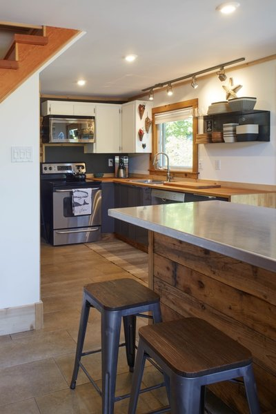 The kitchen was revamped with new modern appliances, including a dishwasher. The custom kitchen island was built from two IKEA cabinets on wheels, topped with an aluminum countertop, and wrapped in salvaged cedar-fence panels.
