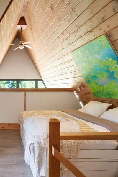 Bathed in natural light, the upstairs master bedroom overlooks views of the living space below.