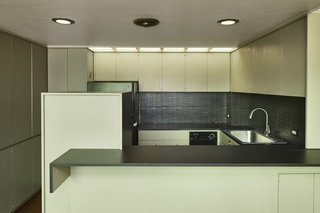 The kitchen features original ergonomic cabinetry, trim work, and recessed lighting.