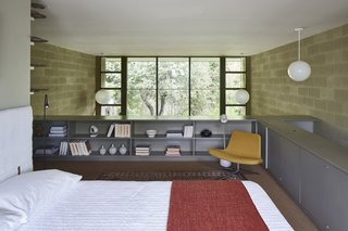 Guardrail-high bookcases provide storage and a sense of enclosure from the living area below.