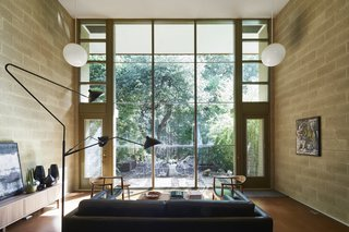 The east side of the living space opens up to a spectacular double-story wall of glass framed by vertical wood mullions and horizontal aluminum H-channels. A six-foot roof overhang protects the glazing from solar gain.