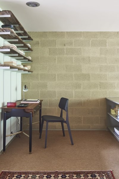 The L-shaped bedroom accommodates a private workspace around the corner.