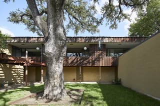 A massive oak tree is the focal point of the entry courtyard. The entrances to each unit are sheltered beneath the overhanging second-story balcony.