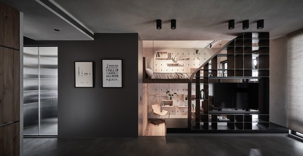 This view from the open-plan living space shows the loft bed and sunken office on the right, as well as the storage room illuminated by a window on the left. The storage room is opposite the entrance.