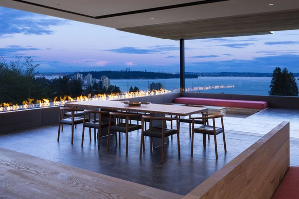 A dramatic outdoor linear fireplace continues from the dining area to the sunken lounge.