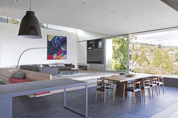 """Elevated on an engineered hardwood floor, the living room is smartly furnished with a Flex Form """"Beauty"""" sectional sofa, Minotti """"Sullivan"""" coffee table, Kurva """"The Bow Lamp,"""" and a hand-woven wool rug by Paulig for Salari."""