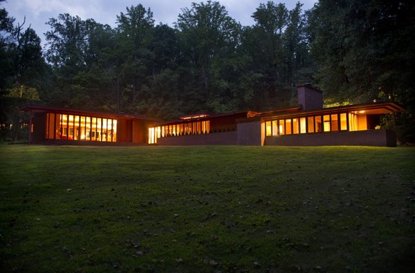 A nighttime view of the home seen from the northeast. To the right is the bedroom wing extending north. To the left is the living room wing stretching to the east.