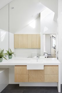 """The master bath is outfitted with a Caesarstone """"Snow"""" countertop and hoop pine plywood cabinetry."""
