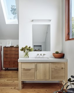 Like the kitchen, the closet vanity features stained white-oak cabinetry.