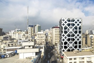 Wrapped in an energy-efficient, double-skin facade of glass and composite aluminum panels, this 12-story office tower in Tehran features a pattern referencing the motif a mandala.