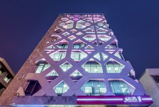 The two skins are spaced approximately two a half feet apart, creating room for the installation of LED backlighting that illuminates the building like a beacon at night. The combination of blue lighting and the patterned facade are evocative of Persian blue mosaic work.