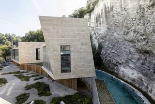 """A narrow creek was carved into the edge of the rock wall to """"extend nature into the site."""""""