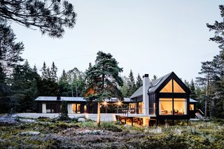 The timber decking that connects the existing cottage to the new volumes emphasizes indoor-outdoor living.